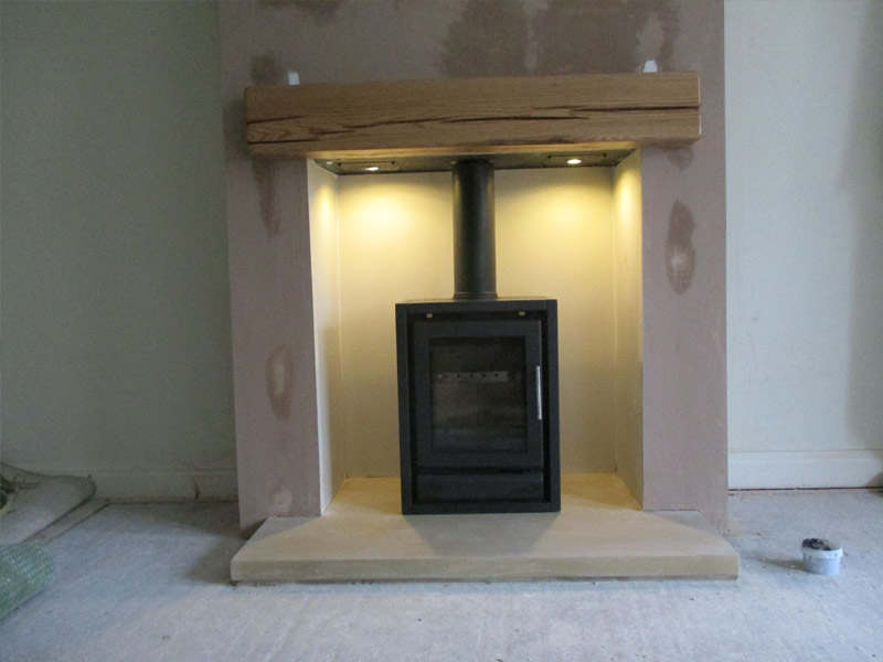 wood burning stove with sandstone hearth and oak beam