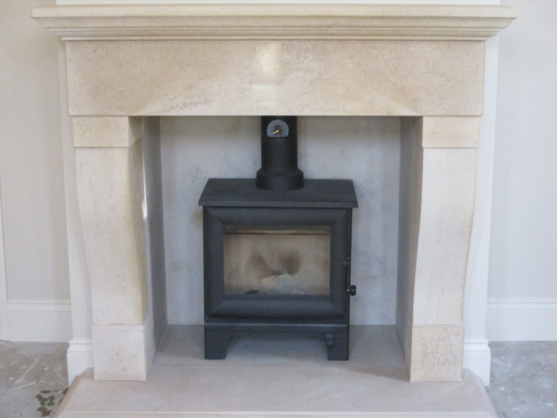 wood burning stove with stone fireplace surround