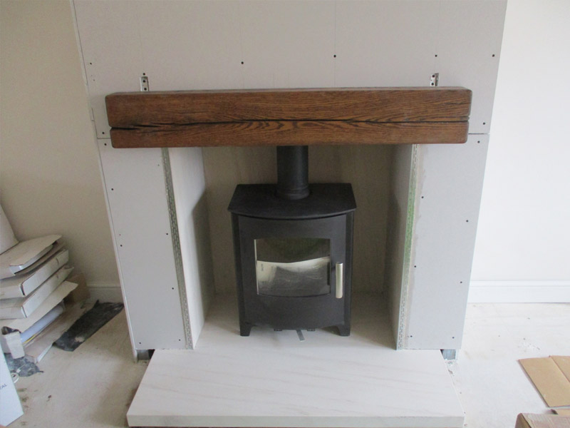 multi-fuel stove with stone hearth and oak beam