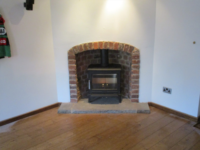 multi-fuel stove on stone hearth with brick chamber