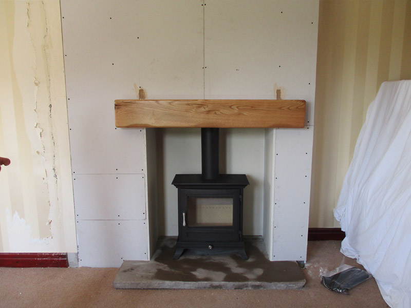 wood burning stove with stone hearth and false chimney breast